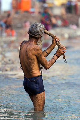 A sadhu wrings his dreadlocks while bathing in Pushkar Lake, Pushkar, Rajasthan, India