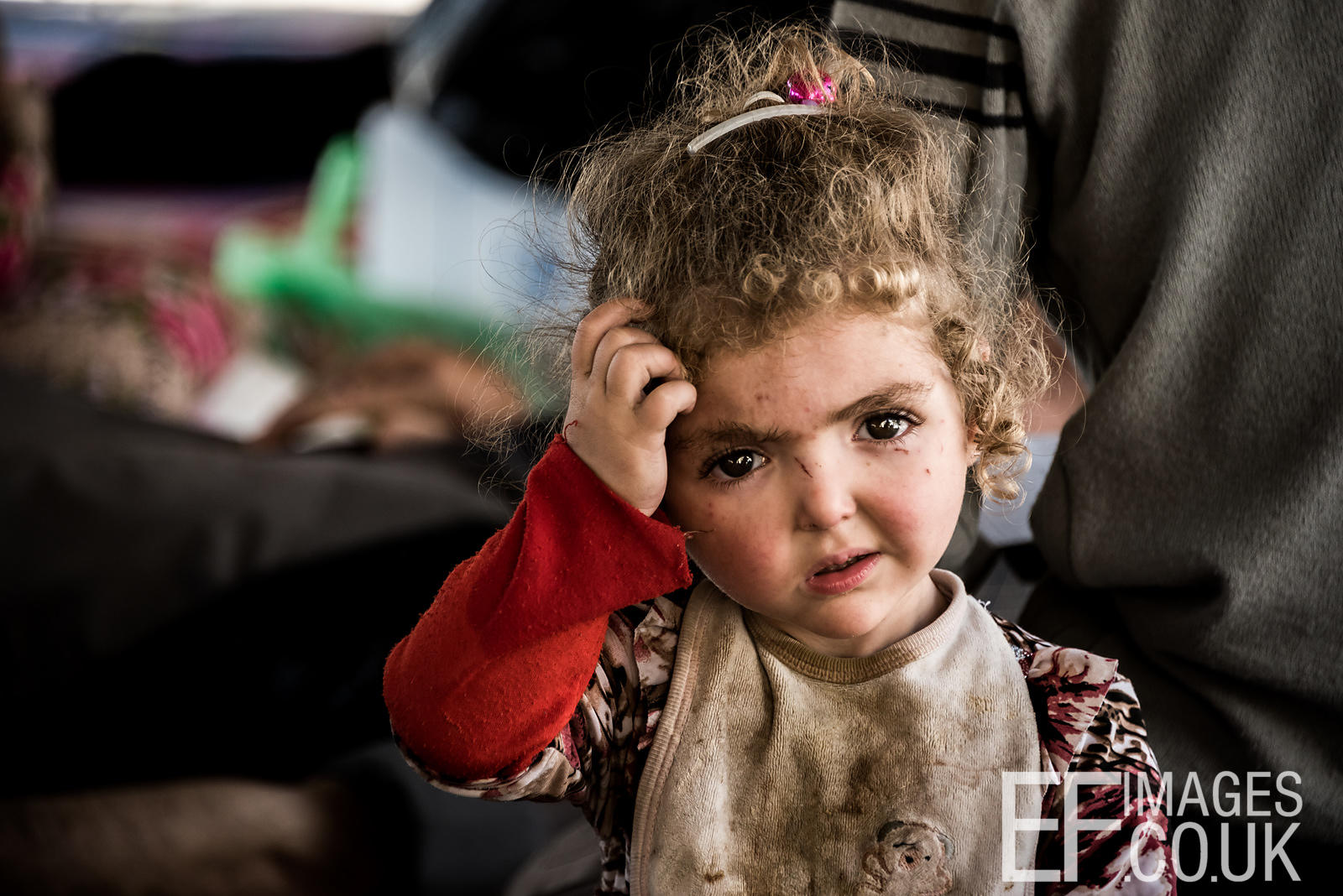 Confused little girl resting at a civilian muster point outside the Tammuz district of West Mosul having escaped ISIS and coalition forces bombardment with her family that morning. May 2017