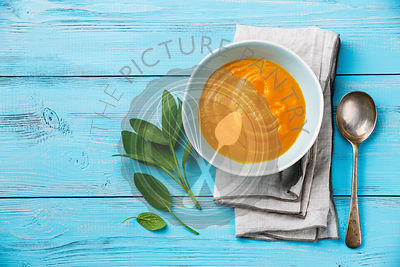 Pumpkin soup with sage on blue wooden background Copy space