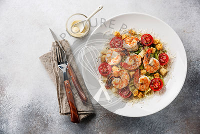 Caesar salad with Shrimp on gray background copy space