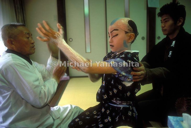 Kabuki kid applies makeup before a performance.