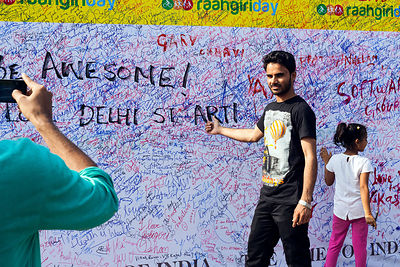 India - New Delhi - People photograph each other in front of a wall covered in graffiti on a road blocked to cars in a section of Connaught Place during a Raahgiri Day
