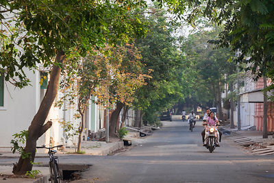 A man and a woman on a motorbike ride through the picturesque streets at dawn, Pondicherry, India