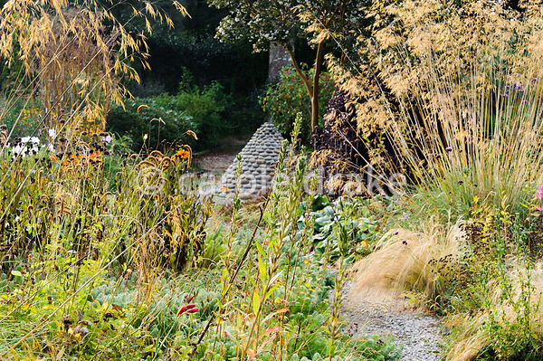 The flower garden featuring fountain-like flowerheads of Stipa gigantea, golden oat grass, plus many other grasses and herbaceous perennials plus a sculptural concrete cone decorated with cobbles.