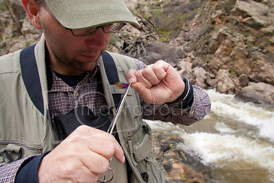 Fisherman tying a fly to his line