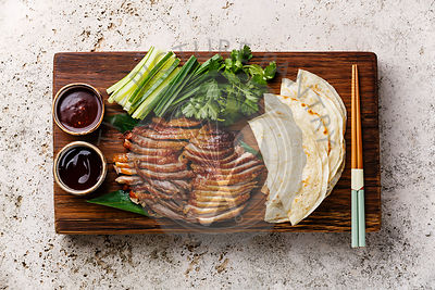 Peking Duck served with fresh cucumber, green onions, cilantro and roasted wheaten chinese pancakes with sauce Hoysin on wooden board