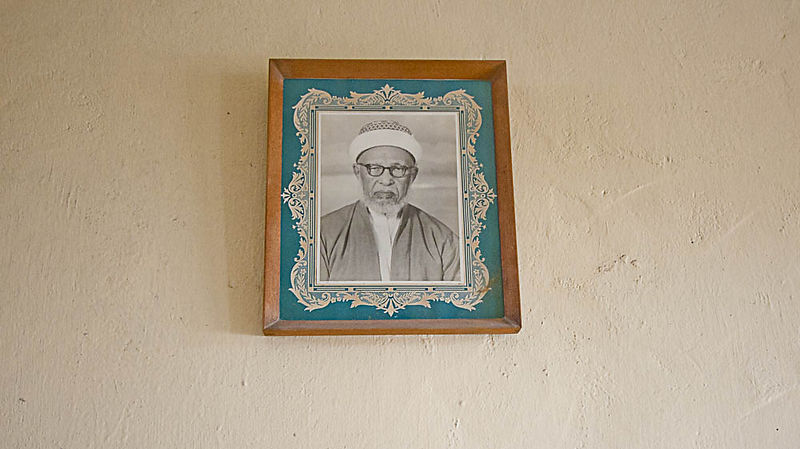 A portrait of a family elder adorns the walls of Amina's home. Commercial portrait photographers were plentiful in Zanzibar at the turn of the century. The interdependence of the community is a cornerstone of Sunni Shafi'i Islam, which 95 percent of Ng'ambo's population practices.