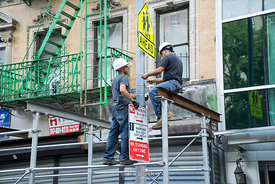 Constructors changing a street sign in Chinatown, NY.