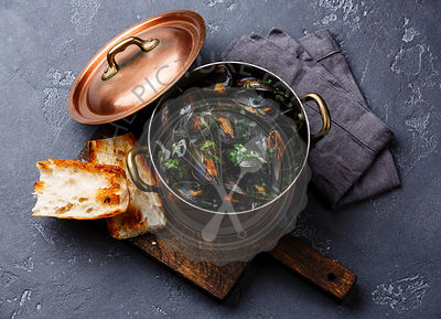 Mussels in copper cooking pan and French Baguette toasts on black stone background