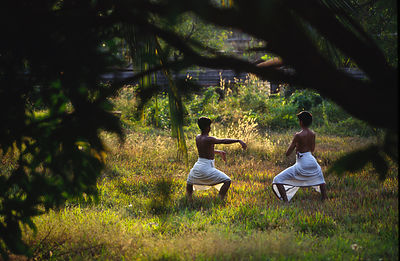 India - Kerala - Students practice their dance steps in the gardens of the Kerala Kalamandalam