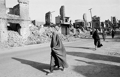 Women in burkha pass ruined buildings in Kabul