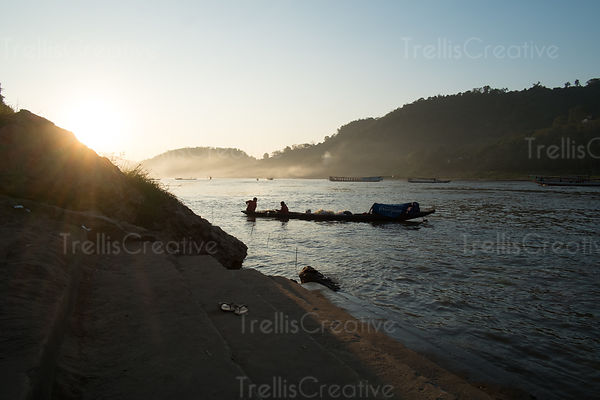 Silhouette of a boat on the Mekong river at sunrise in Luang Prabang