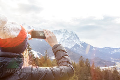 Germany, Bavaria, Zugspitze, back view of woman taking picture with smartphone