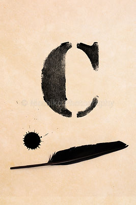 Old black, frayed grunge C - letter, inkblot and black feather on brown paper