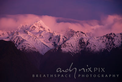 Bright pink alpen glow on rocky snow capped mountain peaks