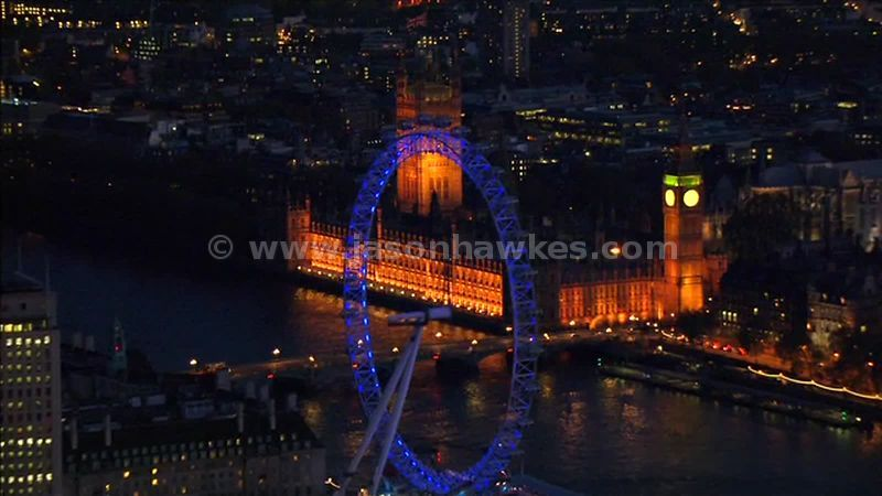 Aerial footage of the Houses of Parliament and London Eye at night, London, England, UK