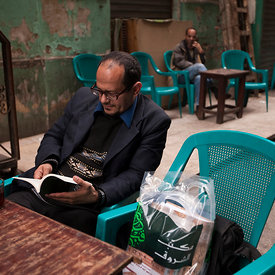 A man reads a book at a table at the Zahrat al-Bustan cafe, Cairo