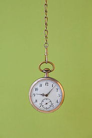 Gold pocket watch against green background.