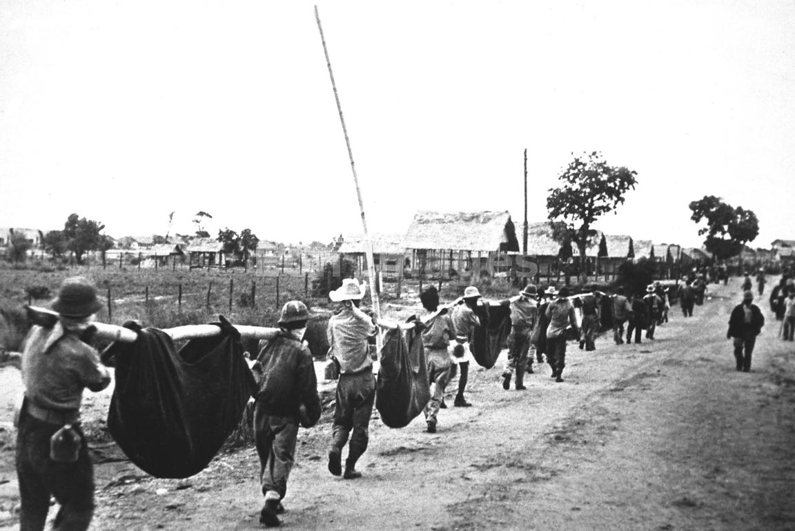 Allied prisoners of war carry comrades in slings in Philippines