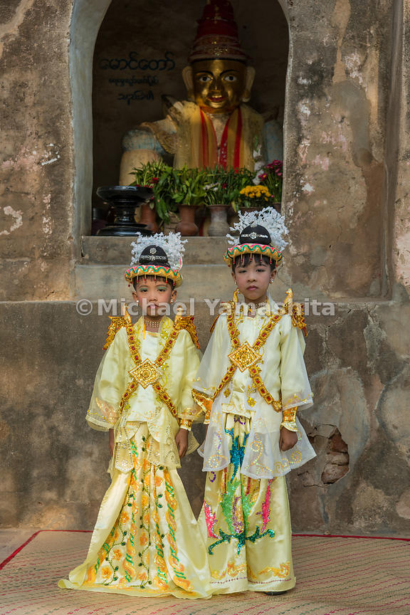Two boys in princely attire at a shinpyu ceremony. Every Buddhist male from around the age of five to 19 has to enter the monastery as a novice once in their lifetime. The ceremony follows a well-known legend in which the Buddha himself stripped his son of garish attire, replaced the boy's clothing with monk's robes and guided him towards a monastic life of detachment. This was how the Buddha, who had renounced his own royal titles, met his own child's request for a princely inheritance.