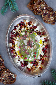 Baked Camembert with Gorgonzola Hazelnut Pesto served with red wine and crackers.