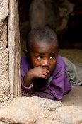 Rwandan toddler in house doorway. Rwanda.