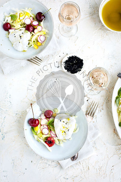 Cherry Burrata Salad served with a Lemon Vinaigrette and Rosé Wine.  Photographed on a off white/white plaster background.