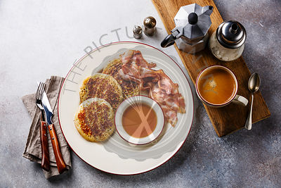 Breakfast with pancakes, bacon, maple syrup and black coffee