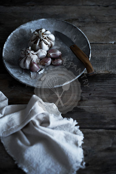 Garlic bulbs in a gray bowl, on a vintage wooden table