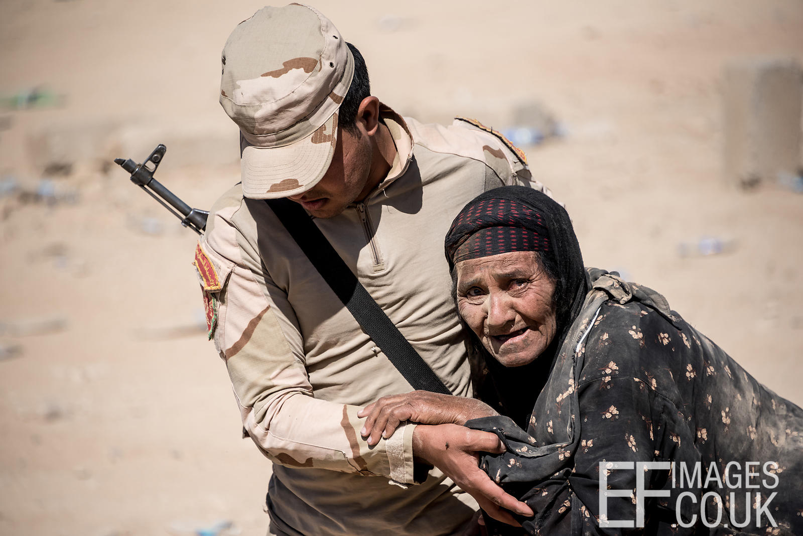 Iraqi Army Soldier helping an old woman to reach a field hospital after she fled her home in Mosul that morning to escape the conflict with ISIS. Mosul, Iraq, 7th May 2017