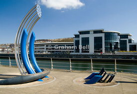 sculpture besides river tawe with the new SA1 development in the distance, swansea, south wales, uk