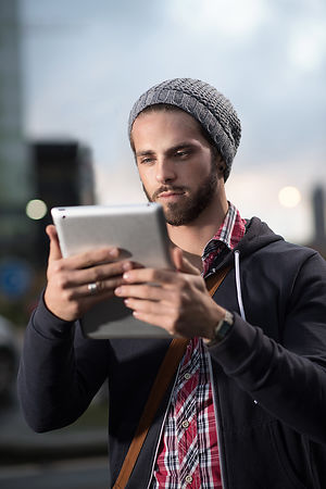 Young stylish man using a digital tablet in the city