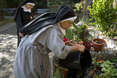 Mother Escolastica (in overall) and Mother Noelle gardening