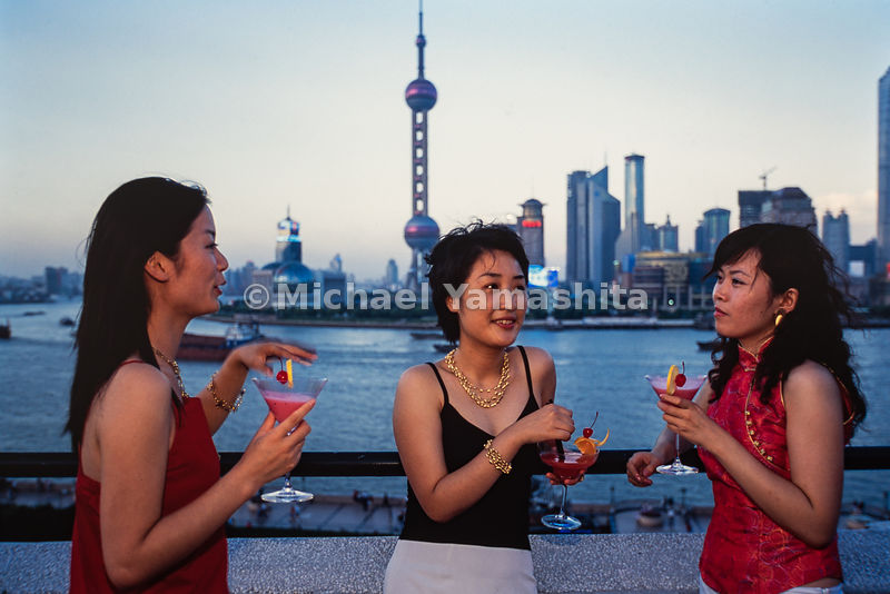 Models pose in front of the Shanghai cityscape across the Yangtze River in China.