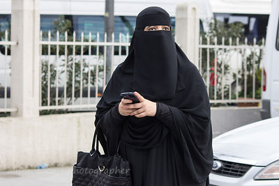 Women in orthodox moslem dress using cell phone