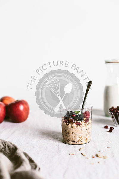 A clear glass of apple muesli topped off with berries is photographed from the front view.