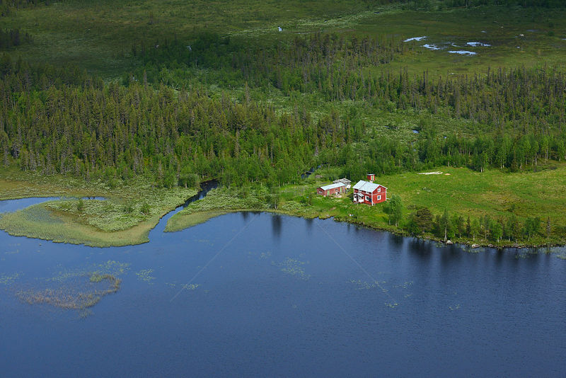 Aerial view of house near lake surrounded by peat bogs and taiga boreal forest, Sjaunja Bird Protection Area, Greater Laponia Rewilding Area, Lapland, Norrbotten, Sweden, June 2013.