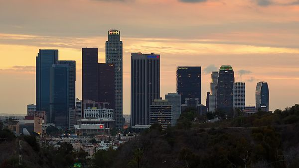 Medium Shot: A Crimson Orange Sunset Decorated With Several Cloud Fronts & High-Rises of Downtown L.A. (Day To Night)