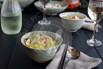 Golden Fennel Soba Noodle Soup is served with quick pickled veggies and white wine. Photographed on a black wooden background.