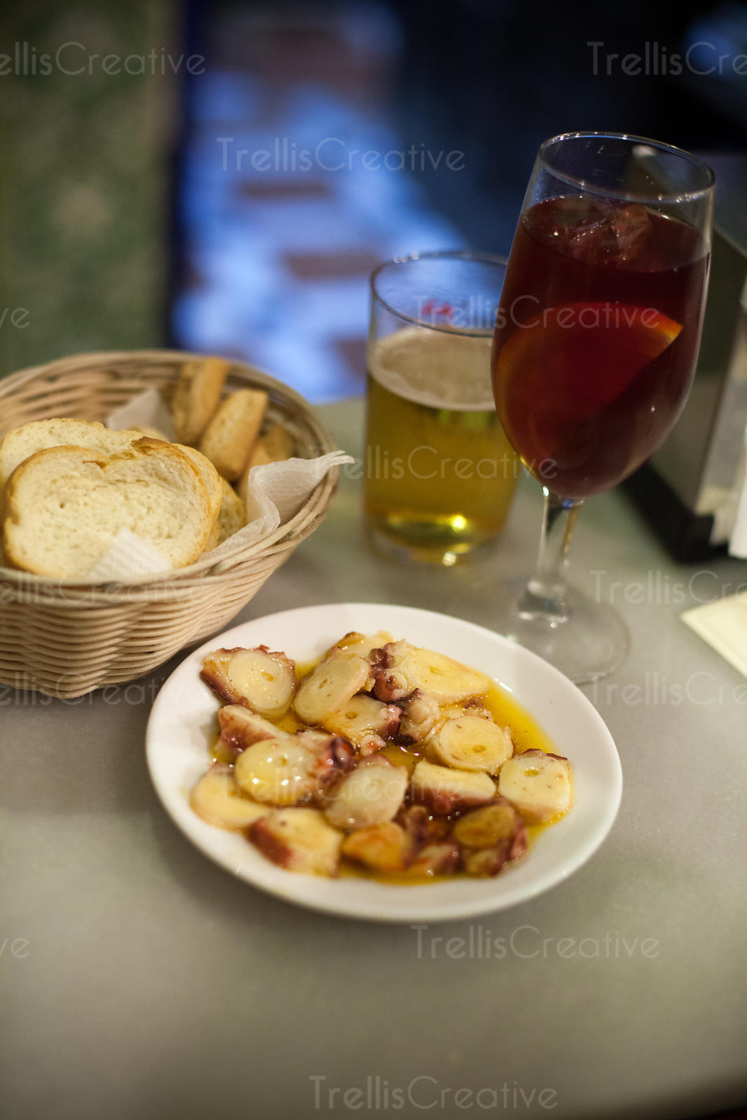 Spanish tapa of octopus with red wine in glass on table