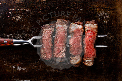 Slices of grilled meat barbecue steak Rib eye on meat fork on dark metal background close-up