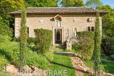 A grass path leads between newly planted cypress trees and clipped phillyreas to the Cloisters. Iford Manor, Bradford-on-Avon, Wiltshire