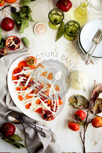Jicama Persimmon Pomegranate Salad with Guava Chevre Vinaigrette. Photographed on a rustic white background.