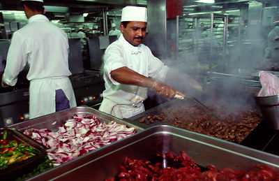 A chef cooks food in the galley on board the P&O Cruise Liner Oriana