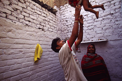 India - New Delhi - A father throws his son into the air