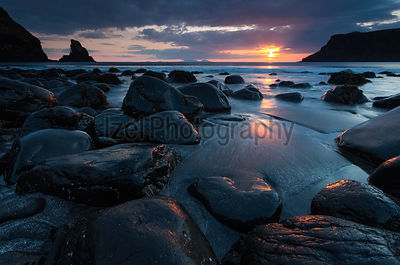 The sun sets over the dark sands and boulders of Talisker Bay in the North West Highlands of Scotland.