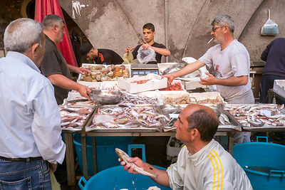 Stallholders sell fish to customers at the Mercato della Pescheria Market