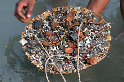 A man pans for money among debris in the Ganges river, Haridwar, India