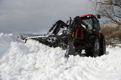 Clearing rural road after snow storm has caused drifting and closed it. Cumbria, UK.