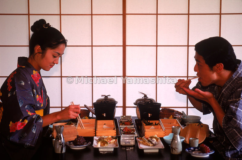 Guests at The Manza Hotel savoring a variety of dishes, some served in bento boxes